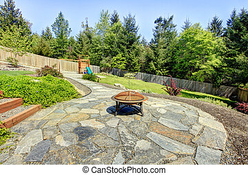 Fenced backyard with stone and fire pit with trees.