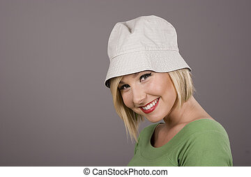 Blonde in White Hat Smiling - A blonde in a green blouse and...