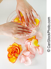 Nail spa - Female holding her hands in water with floral...
