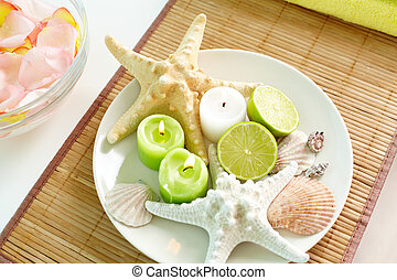 Spa stillife - Candles, citrus and sea-stars lying on the...