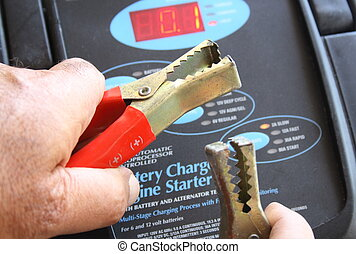 Hands with battery charger - Men s hands holding a battery...
