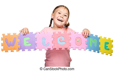 Cute little girl is holding Welcome slogan, isolated over...