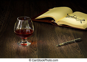 Cognac, cigar and an old book nearby - A glass with cognac,...