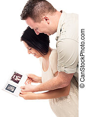Happy pregnant couple with ultrasound pictures - Happy...