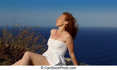 happy redhead woman feeling wind in high lighthouse cliff...