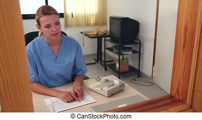 Nurse looking at files at reception - Nurse looking at files...