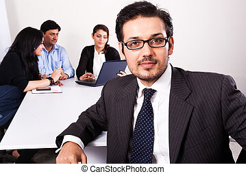 close up of a confident businessman with his colleagues in...