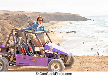 Young woman on buggy on the ocean coast
