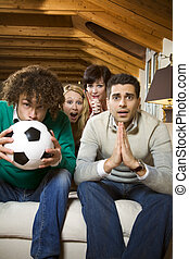 domestic life: group of friends watching a football match on...