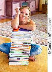 student with a stack of books and computers - a student sits...