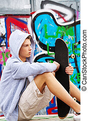 cool-looking young man in front of graffiti - a cool-looking...