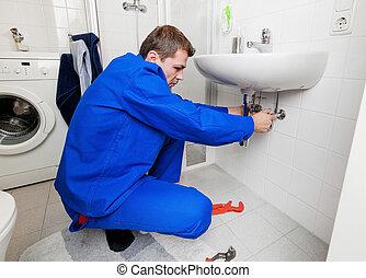 sink plumbing repairs - a plumber repairing a broken sink in...