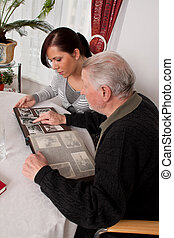 woman looking at a photo album with seniors - a young woman...