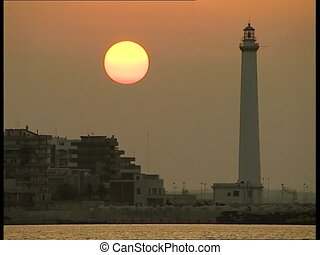 SUNSET at port with lighthouse clos