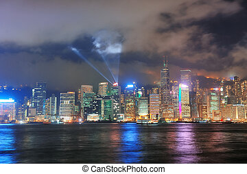 Hong Kong skyline at night with light beams over sea with...