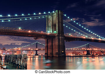 Urban bridge night scene - Brooklyn Bridge closeup over East...