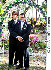 Gay Couple Under Wedding Arch - Newly married gay couple...