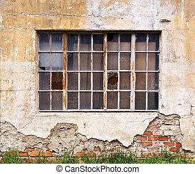 Old facade and window - A large window with broken panes on...
