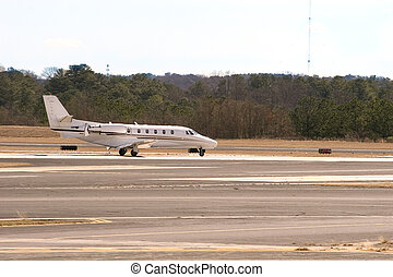 White Jet Taxiing - A white private jet taxxing down the...