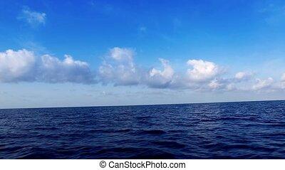 boat saling in deep wavy blue sea
