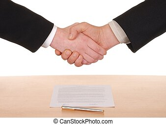 Handshake - hands and signed contract in the background