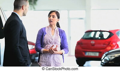 Businessman giving car keys while shaking hands in a...