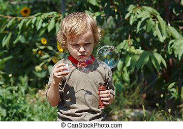 Young cute boy playing with bubbles outdoors on a sunny day