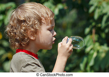 Little boy blowing a bubbles outdoors on a sunny day