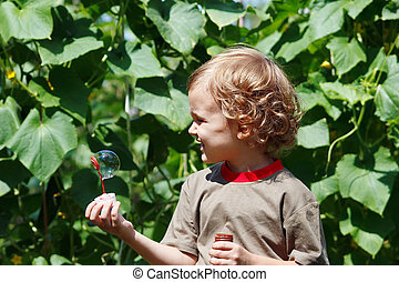 Little boy playing with bubbles outdoors on a sunny day