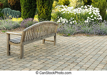 Park bench on paved walk - A park bench sits alone on a...
