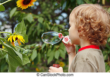 Young blond boy blowing a bubbles outdoors on a sunny day