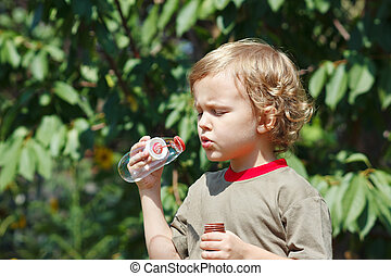 Cute boy blowing a bubbles outdoors on a sunny day