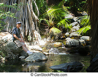 Boomer man resting by desert stream - middle aged male hiker...
