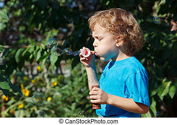 Young boy blowing a bubbles outdoors on a sunny day