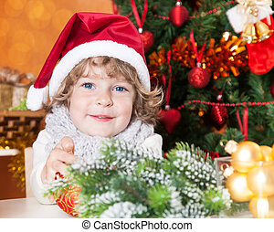 Happy child in Santa hat against Christmas tree with...