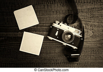 Retro style camera on a wooden table plate with some blank...