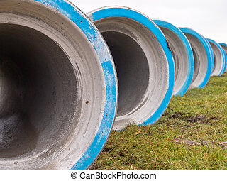 Row of concrete construction pipes on a building site