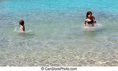 little girls playing in shore beach water in ibiza island