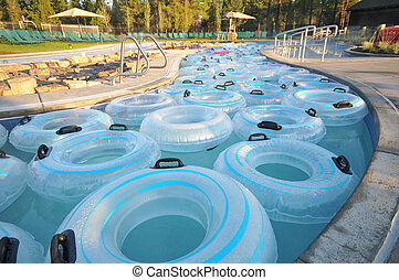 Many inner tubes floating in pool at water park - Water park...