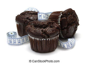 Fattening - Chocolate Muffins with tape measure isolated on...