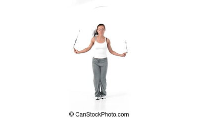 Woman jumping with a skipping rope against a white...