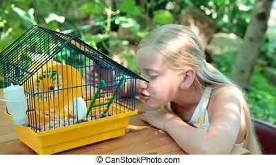Pet Hamster - Little Girl Watching a Pet Hamster in a Cage