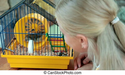 Little Girl Watching a Pet Hamster in a Cage