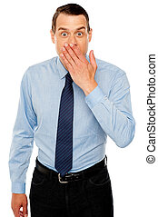 Surprised businessman with hand on mouth, expressing...