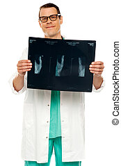 Handsome young surgeon holding x-ray