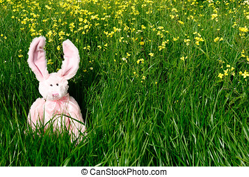 Toy Easter bunny on green grass