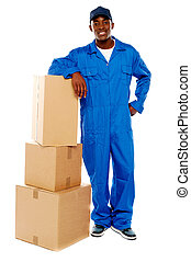 Courier boy standing beside boxes against white background,...