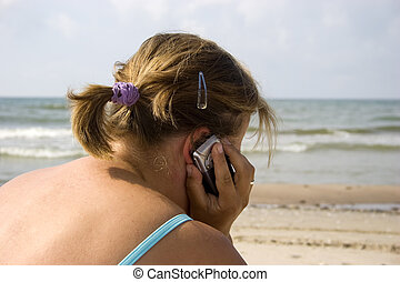 Woman talking by phone in beach