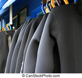 Wetsuits - A row of wetsuits hanging up to dry