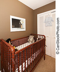 Cherry wood baby crib in nursery interior.